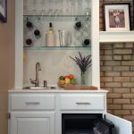 black built-in mini fridge classic white wooden cabinet cystal glasses decorative flower and fruit brick wall