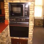 black built in toaster oven antique style kitchen brick walls wooden kitchen countertop