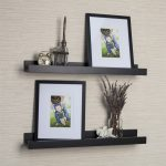 black metal picture ledge shelves decorated with photo frames and vase and clock and art collection