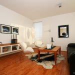 black sofa white chair table rug long cabinet