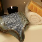 blue cobblestone draining soap dish decorated with aromatic candle and towel for bathroom accessories