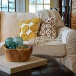 bold white pottery barn sofa slipcover design with geometrical cushion pattern and log tray and black leather pouf coffee table and wooden wall and glass window