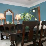 chairs table blue wall mirror lamps rug