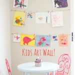 cheerful displaying kids art idea on white wall with letter decoration and pictures section with pink chairs and round white table