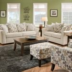 classi living room design with large glass windows and wall picture and patterned cream couch with loveseat set on black area rug