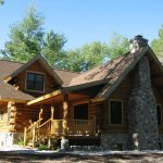 classic and rustic log cabin style home design with stone front accent and brown roof and porch with fence