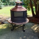 classic chiminea fire pit design in black with copper cover and round base with scrolled legs on patio beneath shady tree