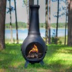 classic designed chiminea fire pit idea on grassy meadow aside lake with tall trees and tripod legs