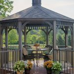 classic gray wood octagon gazebo with low walls and gray wicker chairs and beautiful flowers