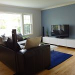 classic living room design with white ikea tv stand idea with blue wall paint and black leather sofa design and blue area rug and wooden floor