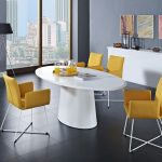 classic modern small oval dining table with orange unique design soft orange  gray tone dining room black floor lamp abstract colorful paintings