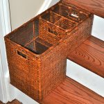 classic tone basket design for stairs made of rattan material with storage partition on wooden steps aside white wall