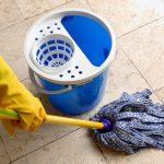 cleaning ceramic tile floors by wet mopping with water and cleaning products white blue bucket