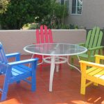 colorful recycled milk jug furniture blue red yellow green outdoor plastic lumber chairs glass top tables brown tile floor outdoor patio furniture