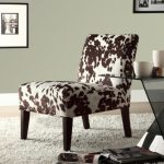 cozy living room design with simple armless cow print chair design on white fabric area rug aside glass end table with gray wall paint and picture