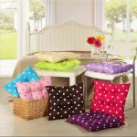 cute floor pillows from ikea design in purple pink brown green and blue with polka dot pattern with rattan basket and wooden stools and bedding set in open plan bedroom