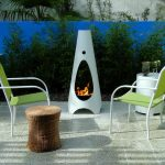 elegant and minimalist white chiminea fire pit design on patio with green chairs and garden and rattan coffee table