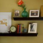elegant black wooden floating shelves lowes design with orange flower with framed photos and clock