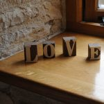 elegant boxy large decorative letters design with wooden Love spelling on wooden banquette before wooden framed glass window with rustic concrete wall