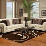 elegant white couch and brown patterned loveseat set with glass coffee table on brown patterned area rug on hardwood floor with glass window