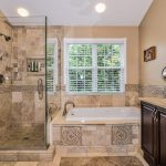 frameless glass enclosed showers natural antique bathroom beige wall color granite floor, walls and countertop