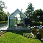 full open plan small lake house design with glass fence and white roofing aside grassy meadow aside lake