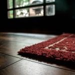 gloomy interior with dark wooden floor with best rug pad for hardwood floor in red color with texture