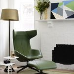 goregeous modern green cozy reading chair design beneath golden floor lamp and white side table beneath white wall with geometrical decoration and potted plant