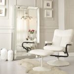 gorgeous white interior design with white wall and pictures and reclining chair and beveled floor mirror aside ceramic