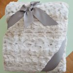 great white faux sheepskin throw desig for gift wth gray ribbon decoration on blue paper