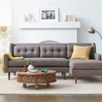 grey 2 piece sectional sofa with chaise in traditional design with tufted back and yellow cushion plus steel standing lamp and wooden coffee table