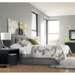 grey upholstery headboard idea modern light black bedside table with single shelf and drawer underneath a table lamp grey bedroom rug idea glossy stained wood floor idea