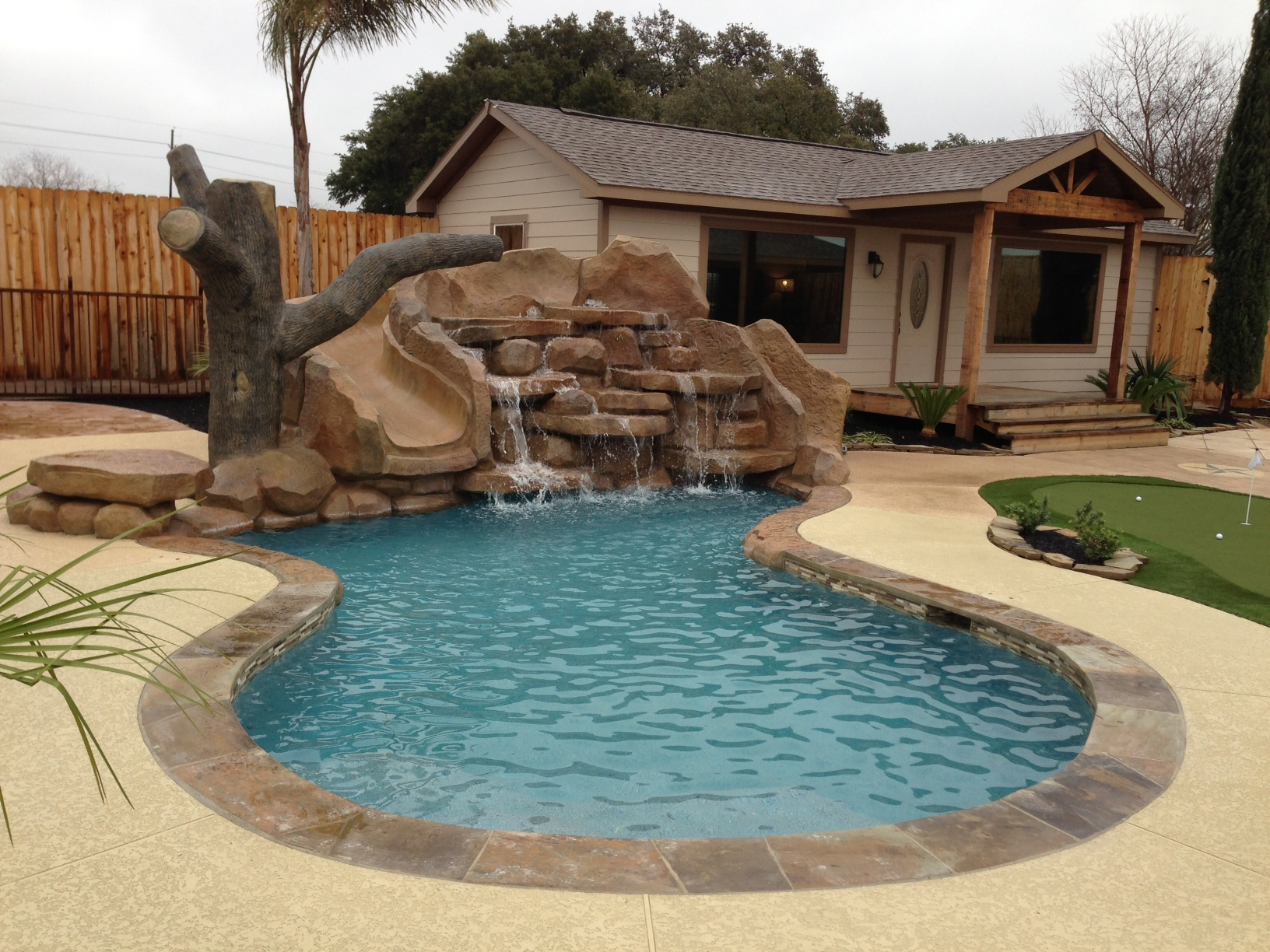 house swimming pool rocks wood waterfall water