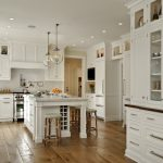 interesting kitchen gallery with white wooden cabinets plus kitchen island with unique bar stoold and jar lighting fixture plus marble countertops