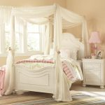 ivory vintage canopy bed frame ivory cushion and bedsheet strip carpet soft pink wall ivory wooden furniture white pink table lamp