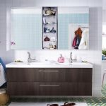 large wooden ikea bath cabinet design with white top beneath storage on blue tile wall with glass window and orchid decoration