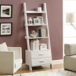 leaning white desk and two drawers painted purple wall frames accessories white sofas rug