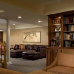 living space basement remodel wood bookshelf brown couches warm color grey carpet