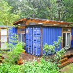 long blue shipping container shed design with sliding glass door and wooden floor in the middle of lush vegetation