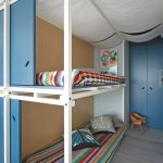 long metal bunk bed for small space design with blue door and rainbow style bedding on gray floor