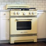 lovable lemonade color retro style appliance idea with cooktop and white storage beneath white brick wall and hardwood floor