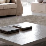 low modern high end coffee tables decorated in modern living room with square white table top and metal leg plus white rug and super comfy couch