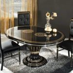 luxurious classic black varnished wooden small oval dining table with wooden lather black dining chairs beautiful decorative flower and gray fur rug