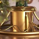 luxurious golden christmas tree stand for real tree with round base and unique curved pole and standing tube in the center
