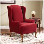 luxurious red wingback chair slipcover design with wooden carved legs and wooden side table with flower and patterned area rug and wooden floor