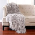 luxurious white faux sheepskin throw on white sofa with tuft pattern on red tile flooring idea