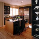 modern avanti compact kitchen design with small island with black chair and black racks  and wooden cabinetry and window glass and hardwood floor