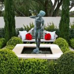 modern garden design with topiary idea with concrete patio with white bench with red white cushions and human statue