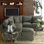 modern grey 2 piece sectional sofa with chaise with cushions decorated with glass top round coffee table and end table plus beige rug