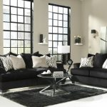 modern living room design with black couch and loveseat set in white with round coffee table and black area rug and table lamps and japanese style glass window